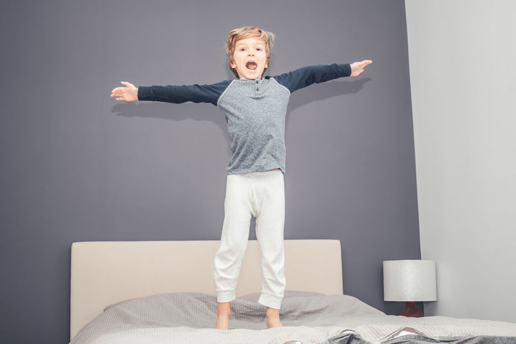 Full length portrait of boy standing on bed against wall