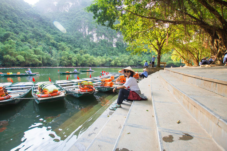 travel at Trang An, Ninh Binh, Vietnam Real People Tree Plant Day Sitting Women Lifestyles Leisure Activity One Person Child Nature Men Water Casual Clothing Full Length Adult Childhood Outdoors