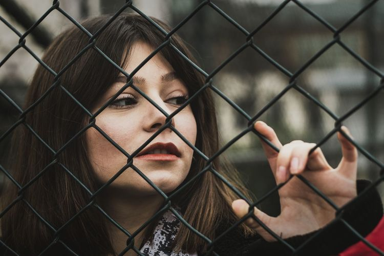 Portrait of man seen through chainlink fence