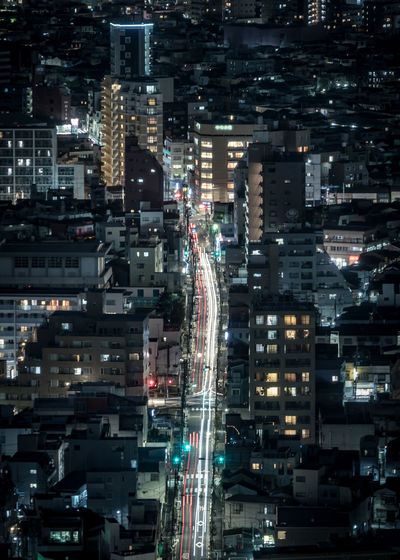 Aerial view of illuminated buildings and road in city at night