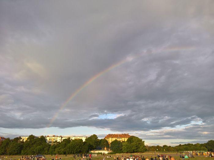 Rainbow over landscape against cloudy sky