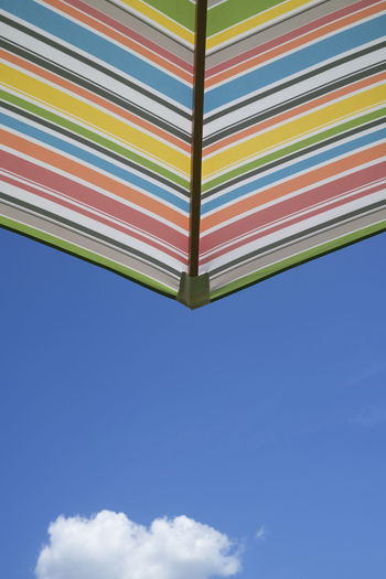 Low angle view of multi colored flags against sky