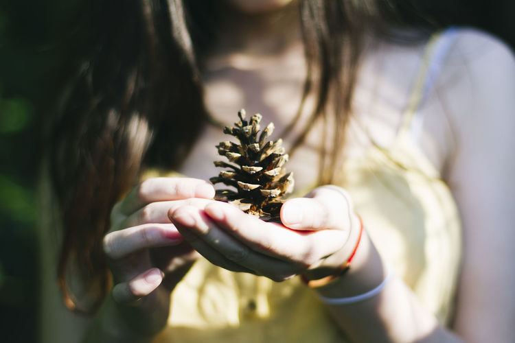 A girl is holding a pine cone Holding One Person Midsection Plant Nature Selective Focus Human Hand Hand Real People Focus On Foreground Close-up Day Front View Women Flower Leisure Activity Outdoors Lifestyles Beauty In Nature Hairstyle Hands Cupped Girl Girlfriend Pine Cones Pine Cone