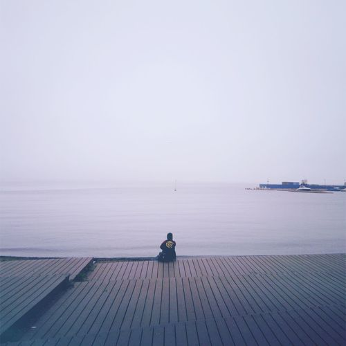 Rear view of man sitting on sea against sky