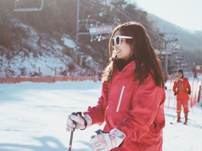 Side View Of Young Woman Skiing On Snow Covered Field
