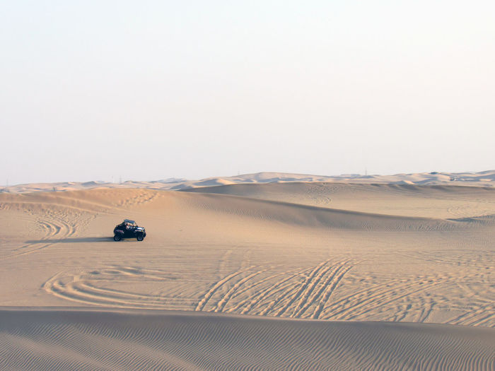 Beach Buggy On Sand Dune In Desert Against Clear Sky