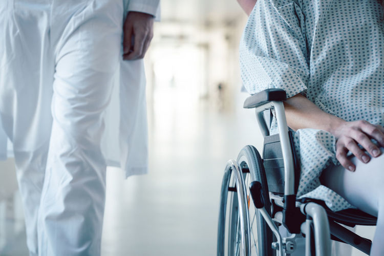 Midsection of male doctor walking with female patient in wheelchair at hospital