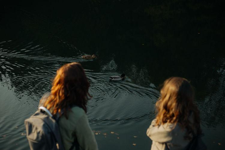 Rear view of women standing in water