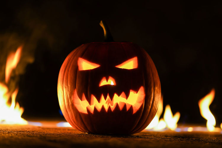 Illuminated jack o lantern with fire in background at night