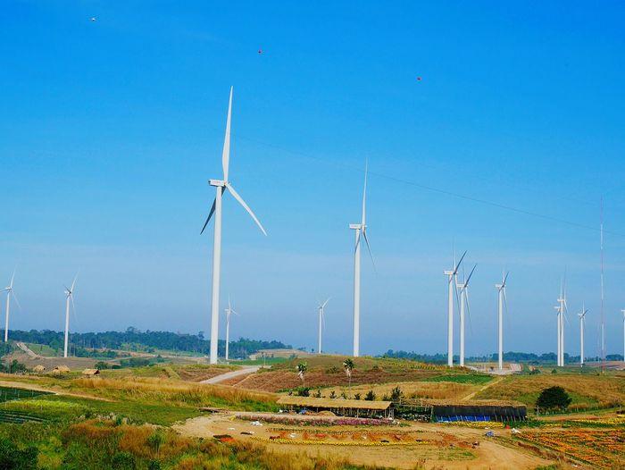 Windmills on landscape against blue sky
