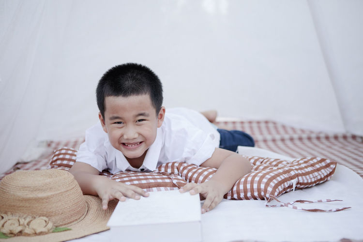 Portrait of boy holding book lying on bed at home