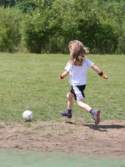 Rear View Of Girl Playing Soccer On Field