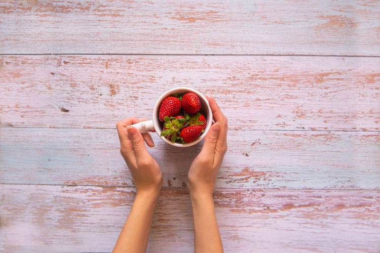 High angle view of woman holding strawberry