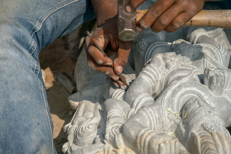 Midsection of man working on sculpture