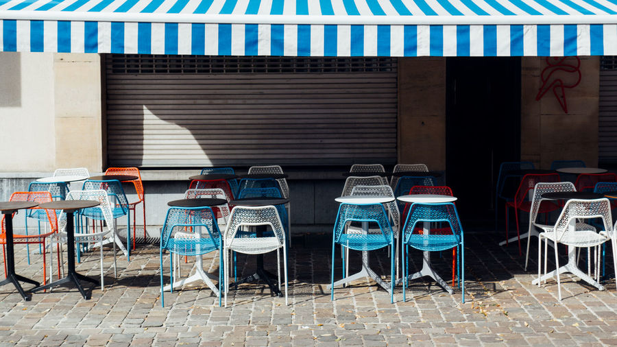 Empty chairs and tables against wall