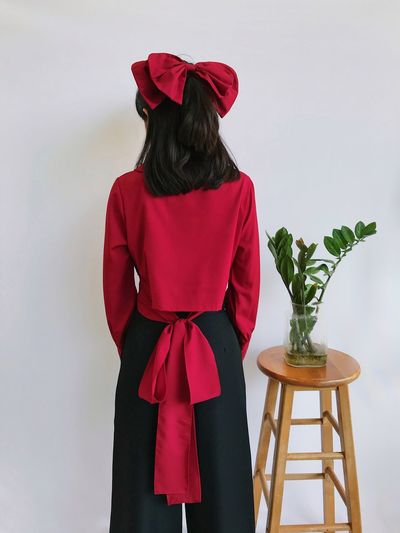 Rear view of woman with red umbrella standing on table