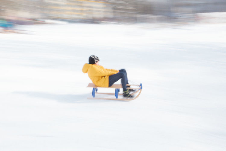 Side view of person riding motorcycle on snow