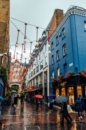 People walking in commercial streets in the Soho, London a rainy day Adult Adults Only Brexit Building Exterior Carnaby Street City Commercial Day England London London Lifestyle Outdoors People Rainy Retail  Shops Sky SoHo #nyc Travel Destinations Umbrella