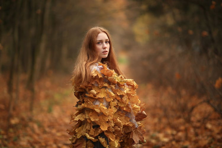 Thoughtful young woman covered with leaves standing at forest during autumn