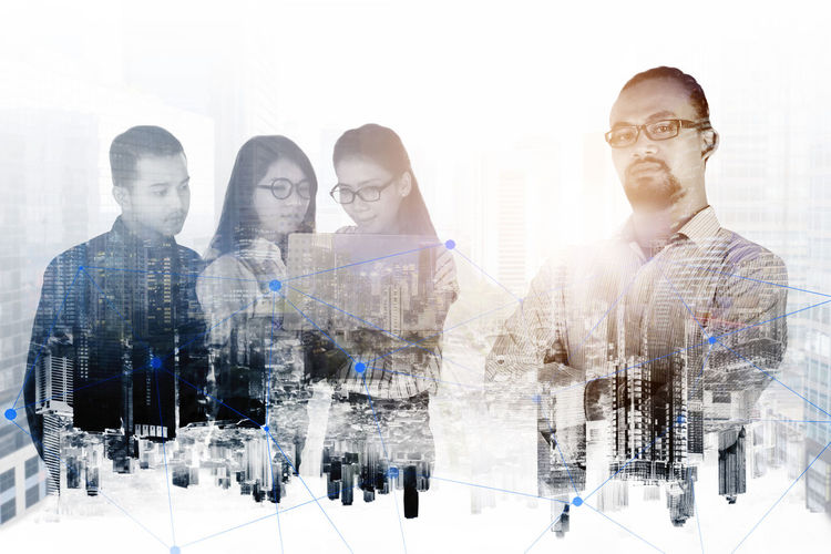 Digital composite image of people standing on laptop