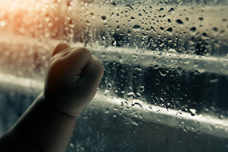 Close-up of hand on wet glass window