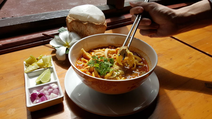 Cropped image of hand holding noodles in bowl on table