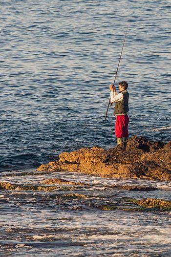 Full length of fisherman standing in water