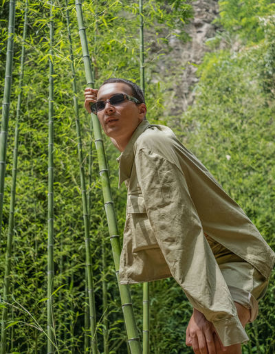 Portrait of man wearing sunglasses standing by plants