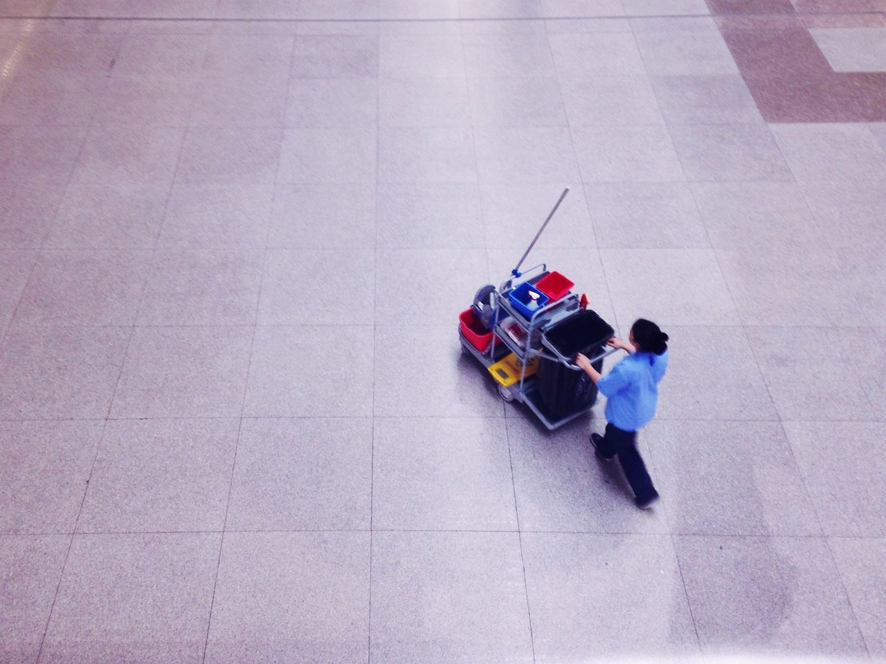 High angle view of female caretaker pushing cart at airport
