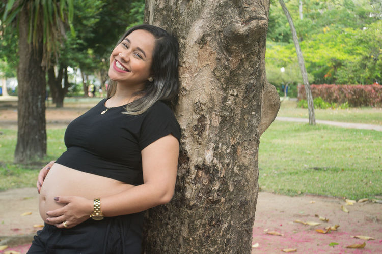 Happy Young Pregnant Woman Standing By Tree Trunk
