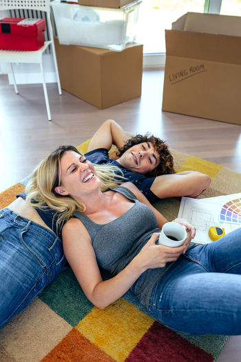 High angle view of couple lying on rug at home