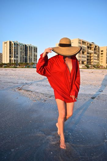 Mature woman wearing hat standing at beach against clear sky