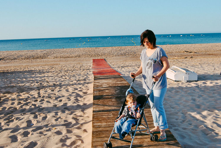 Mother with son in baby stroller at beach