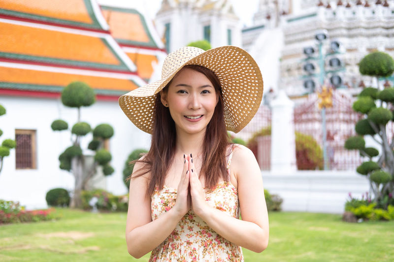 Travel Thailand concept. Young Asian woman with smile greeting in thai style at Wat arun temple Asian  Greeting Thailand Travel Travel Photography Beautiful Woman Casual Clothing Clothing Emotion Focus On Foreground Happiness Hat Looking At Camera One Person Portrait Real People Smiling Sun Hat Teenager Thai Style Travel Thailand Travel Destinations Traveler Young Adult Young Women