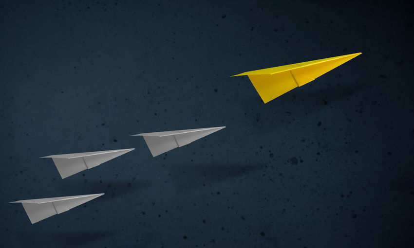 Paper airplanes flying against wall