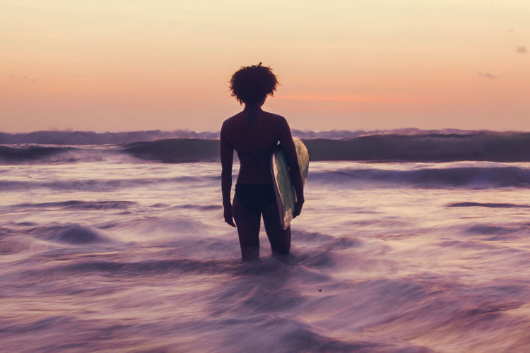 Rear view of woman with surfboard standing in sea during sunset