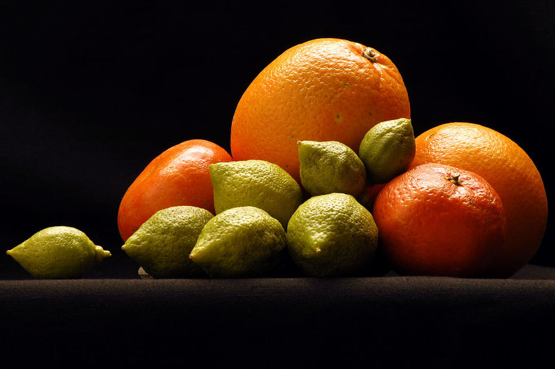 Close-up of orange fruits on table against black background