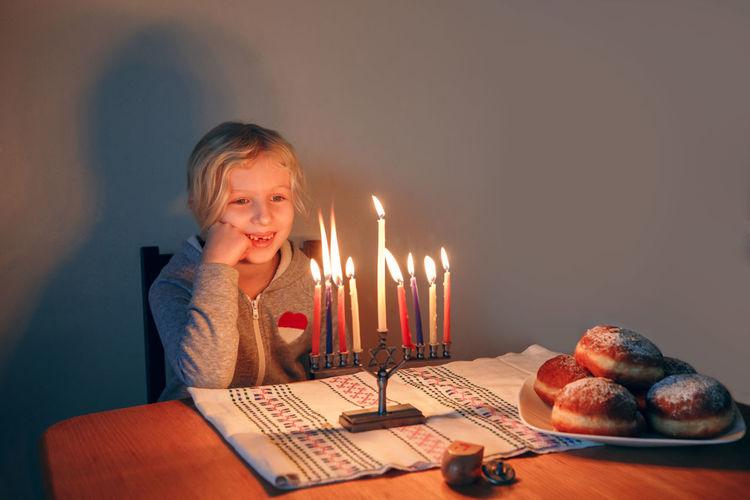 Girl lighting candles on menorah for traditional jewish hanukkah holiday. child celebrating chanukah