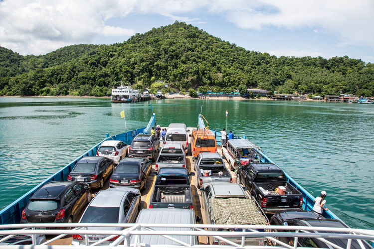Cars On Ferry At River Against Mountain