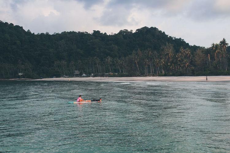 Man floating on sea against sky