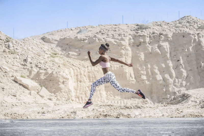 Strong athletic African American Black woman wearing long black and white printed tights and a pink sports bra is sprinting or running on a hot road in a dusty rocky desert background African American Women Athletic Strong Woman Muscles Sunflare Horizon Over Water Desert Dusty Road Mountain Rocks Mountain Range Sprinting Running Jogging Fitness Outdoors Blue Skies Fitnessmotivation