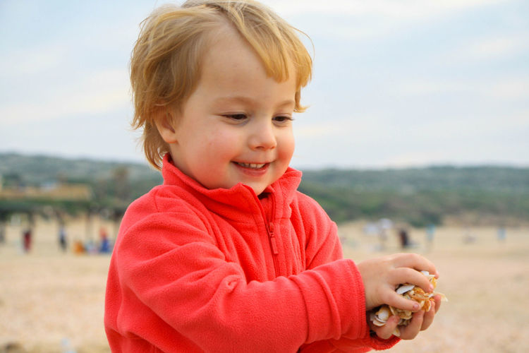 Close-up of smiling girl playing with seashells at beach