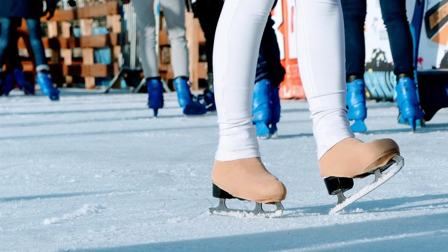 Low section of woman ice-skating on rink