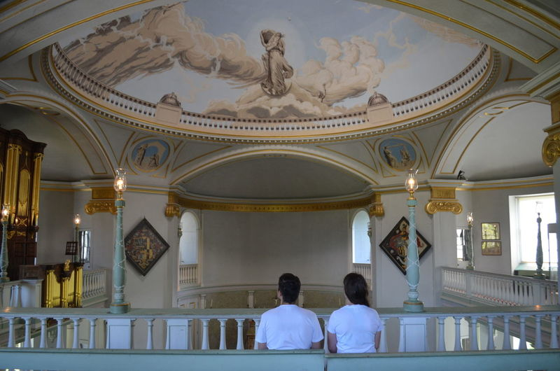 Couple in white sitting on chapel bench,  near lulworth castle, catholic stronghold in england, uk.