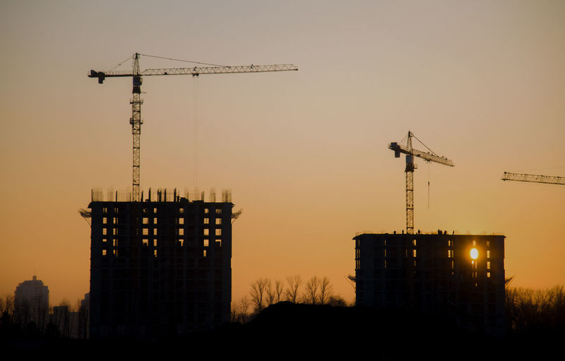 Silhouette crane by building against sky during sunset