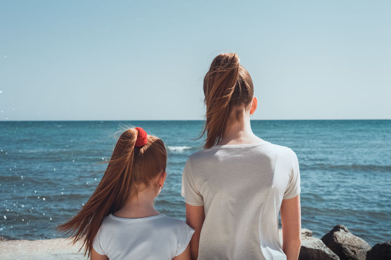Rear view of female friends standing at beach against clear sky