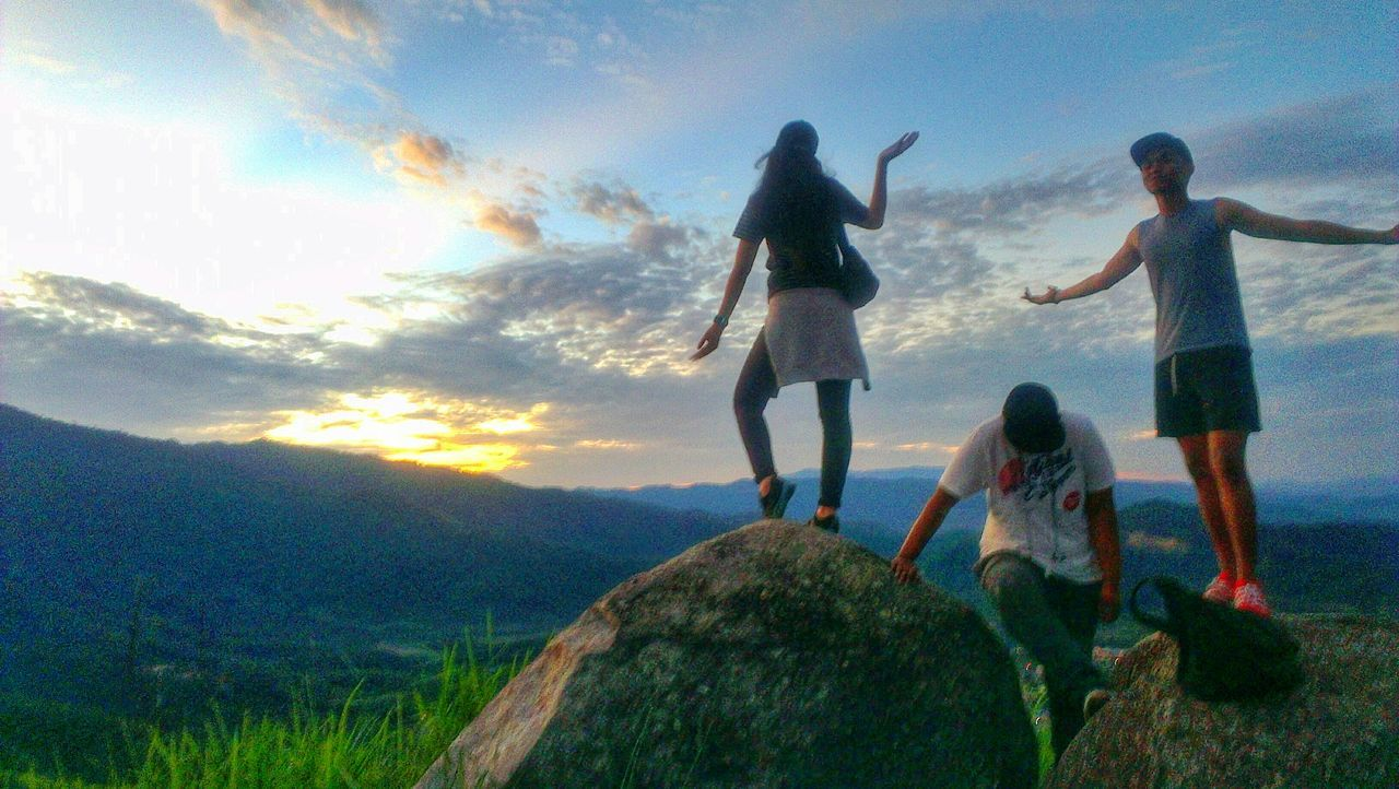 sky, togetherness, cloud - sky, friendship, leisure activity, real people, nature, fun, full length, women, scenics, mountain, outdoors, men, lifestyles, group of people, day, beauty in nature, landscape, grass, young adult, people