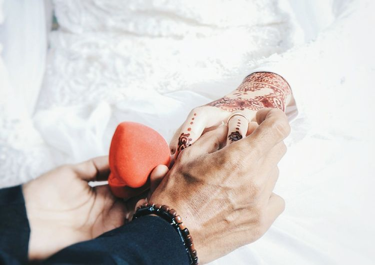 Cropped hands of bridegroom putting ring on bride during wedding ceremony