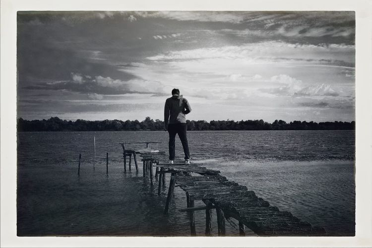 Rear view of man standing on calm lake