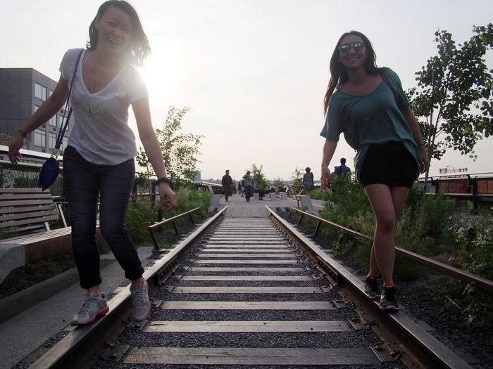 Full length of woman standing on railroad tracks against sky